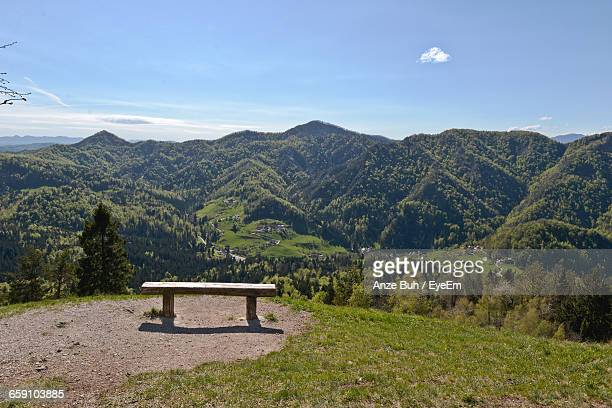 Empty Bench On Landscape Against Mountain Range