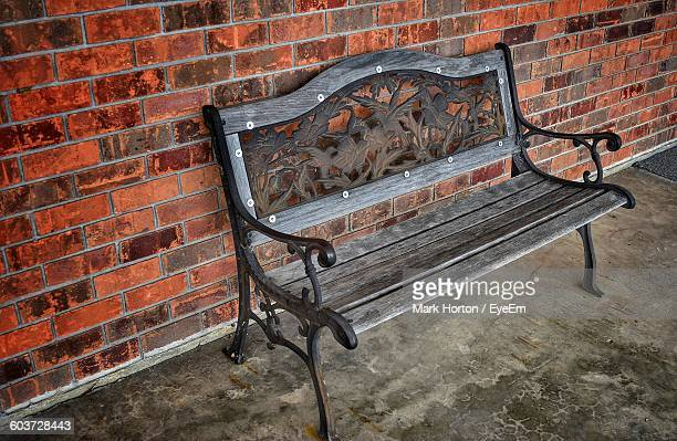 Empty Bench On Sidewalk Against Brick Wall