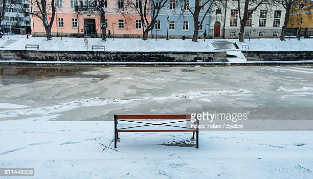 Empty Bench On Snow Against Frozen Canal