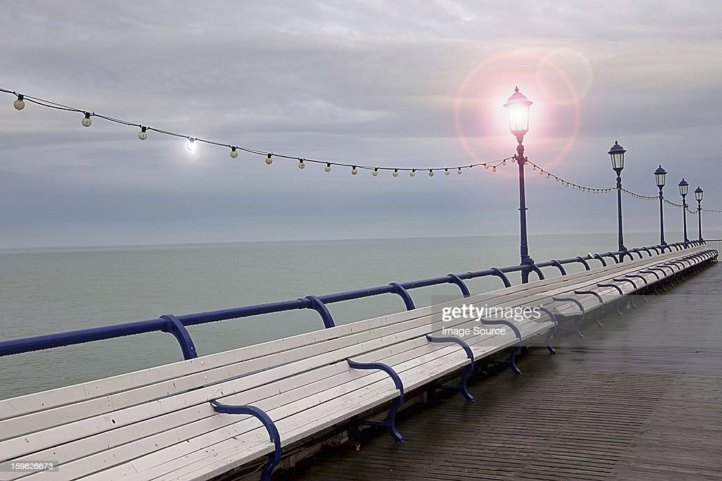 Empty benches on seaside pier, Eastbourne, East Sussex, UK : Stock Photo