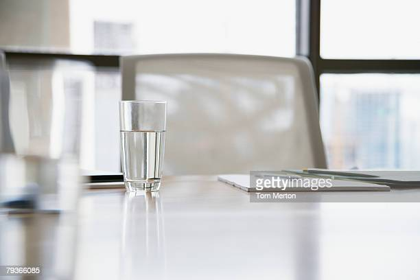 Empty boardroom chair with notepads and glasses of water on table