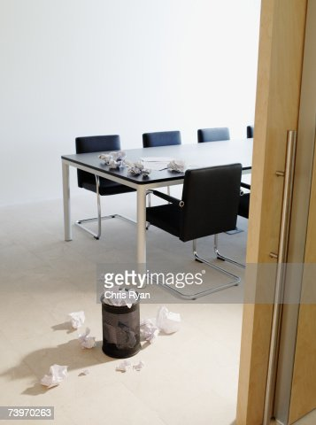 Empty boardroom littered with crumpled papers : Stock Photo