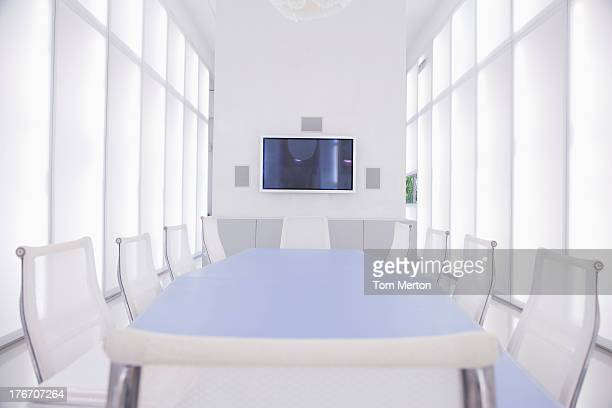 Empty boardroom with large television hanging on wall