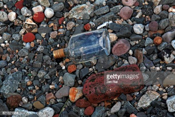 Empty bottle in the pebbly strand of the Hudson river, Jersey city, New Jersey, USA