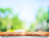 Empty brown wood table top with sun and blur green tree bokeh background, Template mock up for montage of product.