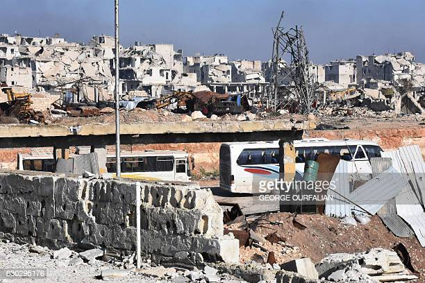 TOPSHOT Empty buses that are going to be used to evacuate Syrians from eastern Aleppo enter the embattled city through the Ramoussa crossing on the...