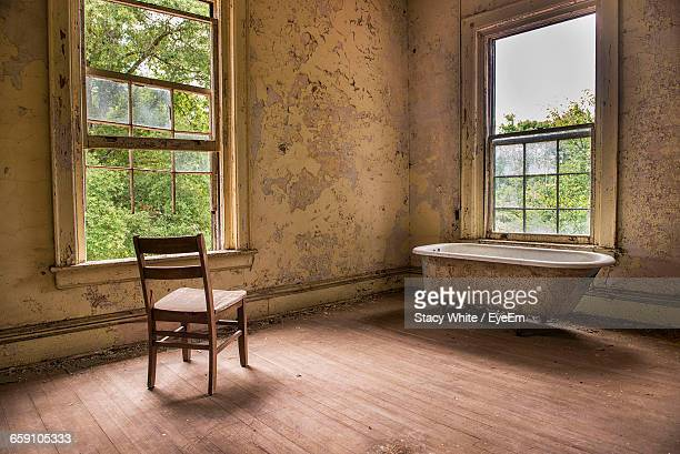 Empty Chair And Bathtub In Abandoned House