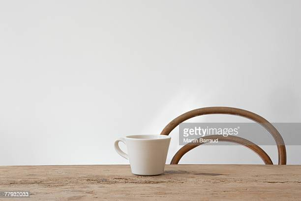 Empty chair and mug on table