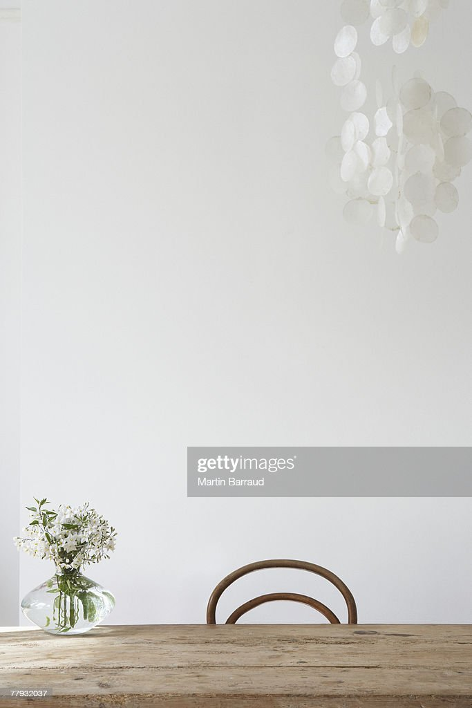 Empty chair and vase on table