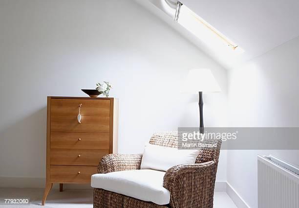 Chaise vide à côté d'une commode
