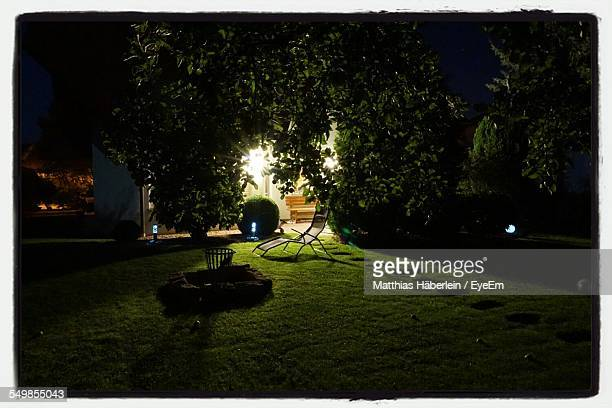 Empty Chair By Illuminated Lamps And Bushes At Lawn