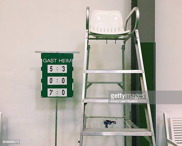 Empty Chair By Scoreboard At Tennis Court
