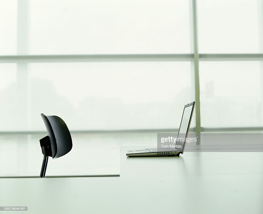 Empty chair in front of laptop on counter : Stock Photo