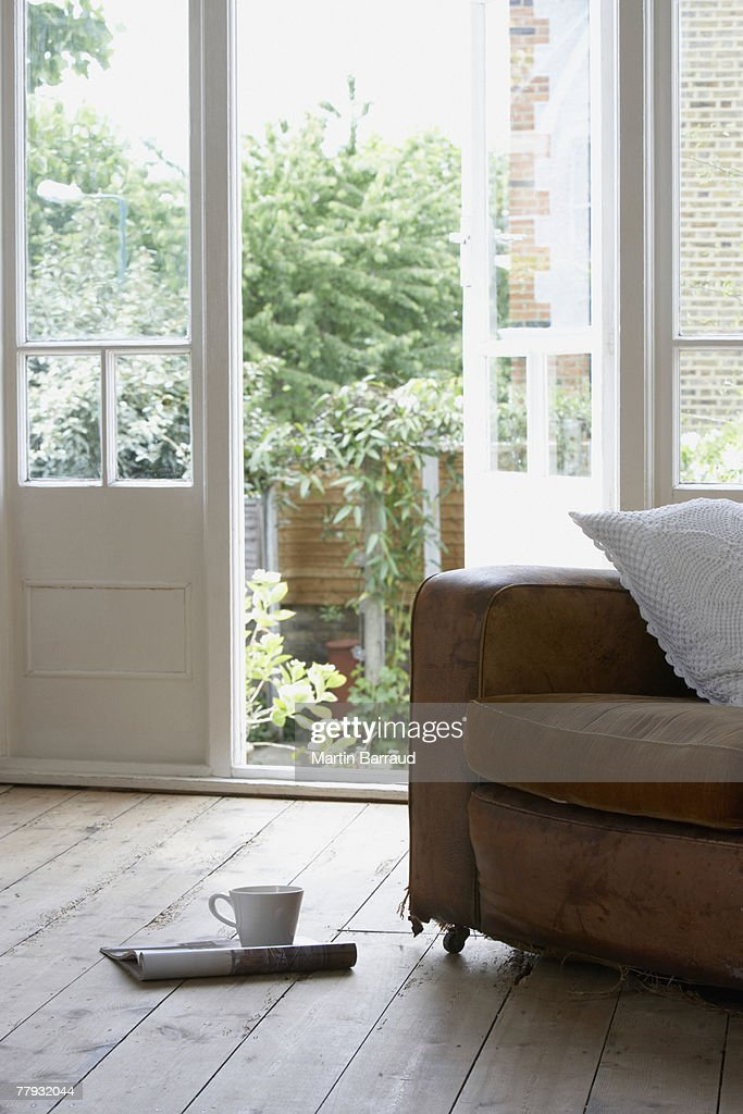 Empty chair with open magazine and mug on floor : Stock Photo