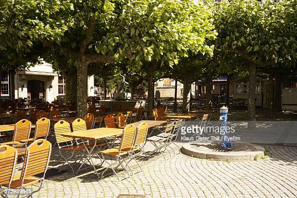 Empty Chairs And Table Arranged On Sidewalk Cafe By Trees In City