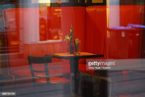 Empty Chairs And Table Seen Through Glass Window Of Restaurant