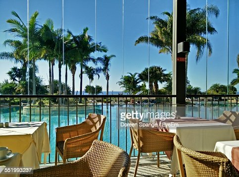 Empty Chairs And Tables Against Swimming Pool