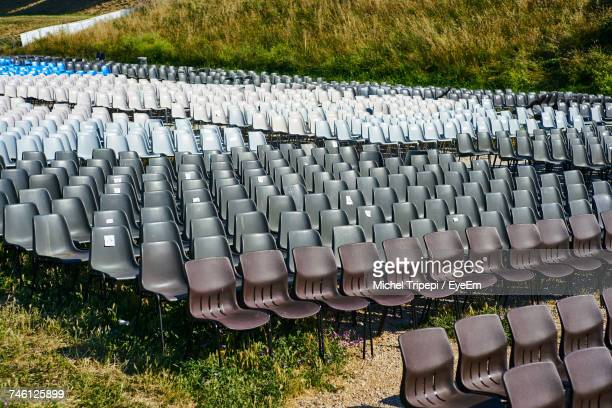 Empty Chairs Arranged On Field