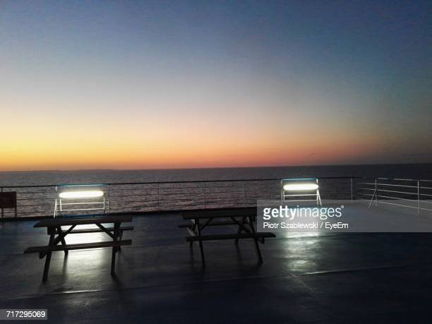 Empty Chairs In Calm Sea At Sunset