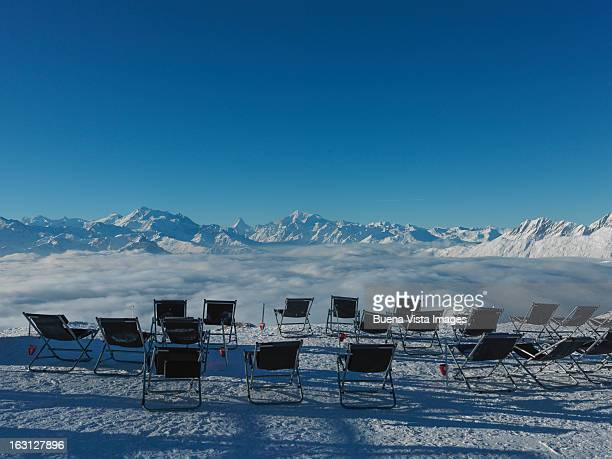 Empty chairs on snow in Swiss Alps.