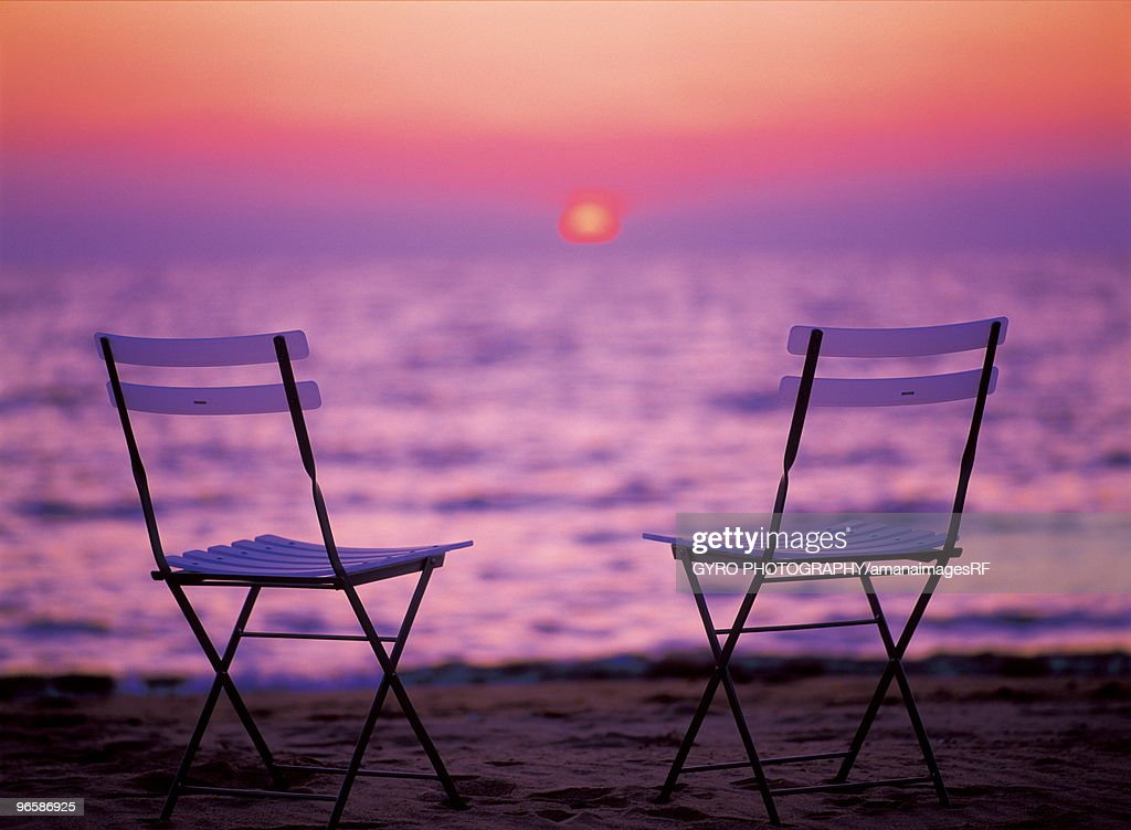 Empty Chairs On The Beach By Sea At Sunset Stock Photo Getty Images