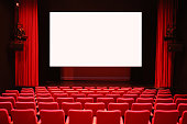 Empty cinema room with red seats and a white screen