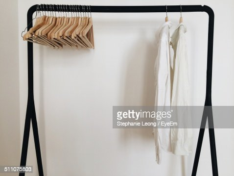 Empty coathangers on rack over white background