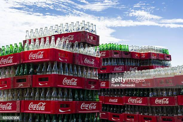 Empty Coca Cola bottles in crates are piling up