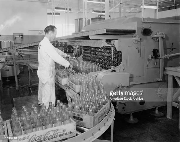 Empty CocaCola bottles on a conveyor belt at a bottling plant circa 1955