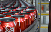 Empty CocaCola Classic cans move along a conveyor to be filled and sealed at a CocaCola Amatil Ltd production facility in Melbourne Australia on...