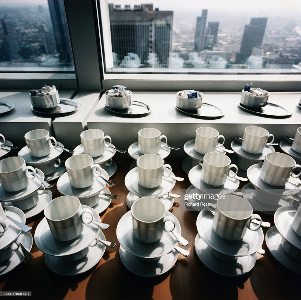 Empty coffee cups stacked on plates in window sill : Stock Photo