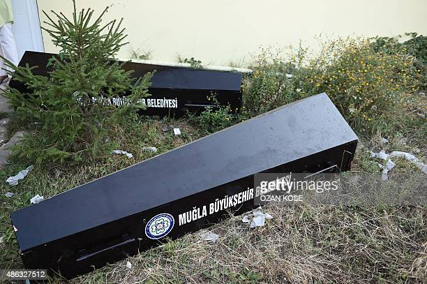 Empty coffins lie on the ground beside the entrance of the morgue in Mugla southern Turkey on September 3 where were taken the bodies of migrants and...