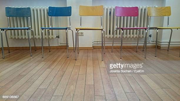 Empty Colorful Chairs On Hardwood Floor Against Wall