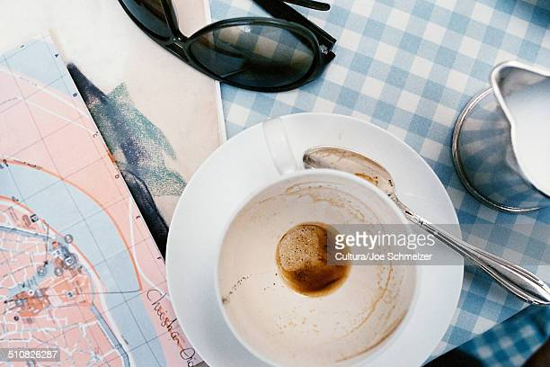 Empty cup and map on cafe table