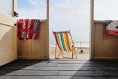 Empty deckchair outside beach hut, rear view