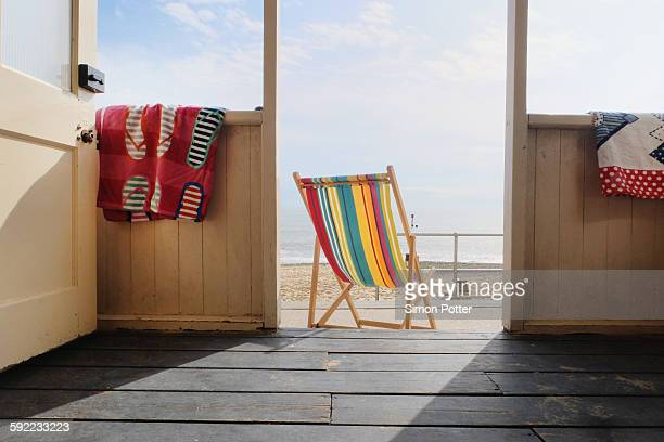 Empty deckchair outside beach hut, rear view