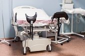 Empty delivery room with bed and medical equipment in the maternity ward at a hospital.