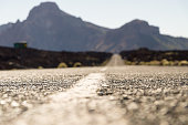 Empty desert road with mountains on background, shallow depth of field