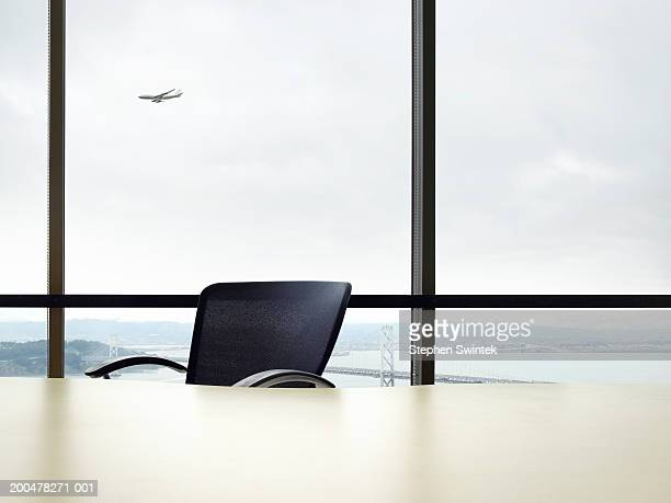 Empty desk, commercial plane flying in background (Digital Composite)