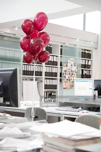 Escritorio vacío con globos rojos vinculados con silla