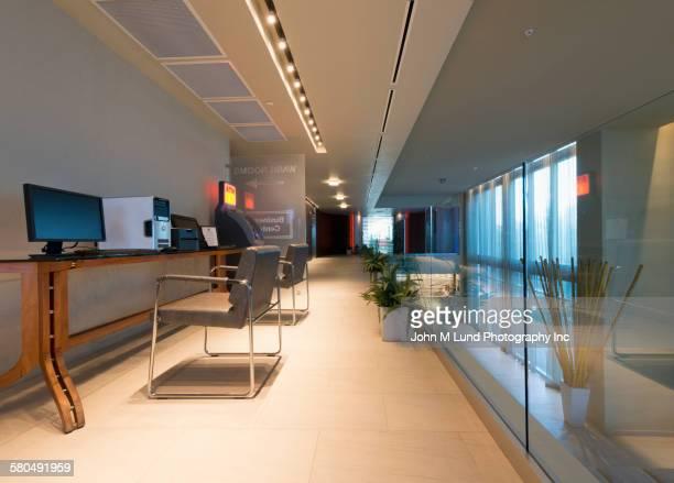 Empty desks in modern office hallway