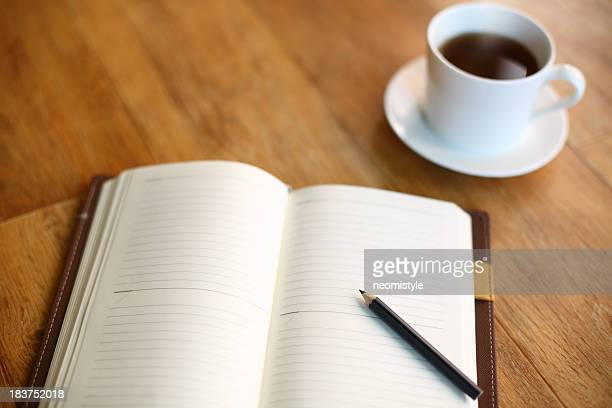 Empty diary with pencil and cup of coffee on wooden table