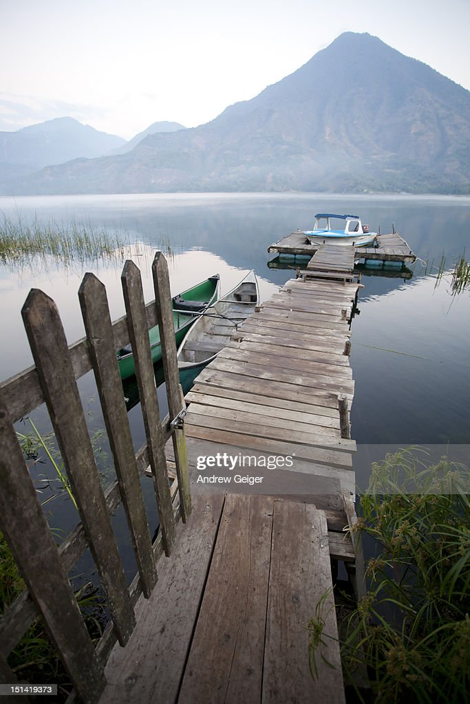 Empty dock on volcanic lake with old boats. : Stock Photo