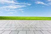 empty floor and green field under blue sky