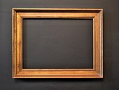 Empty picture frame on black wall