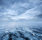 Empty nature background, frozen lake and dramatic sky with copy space
