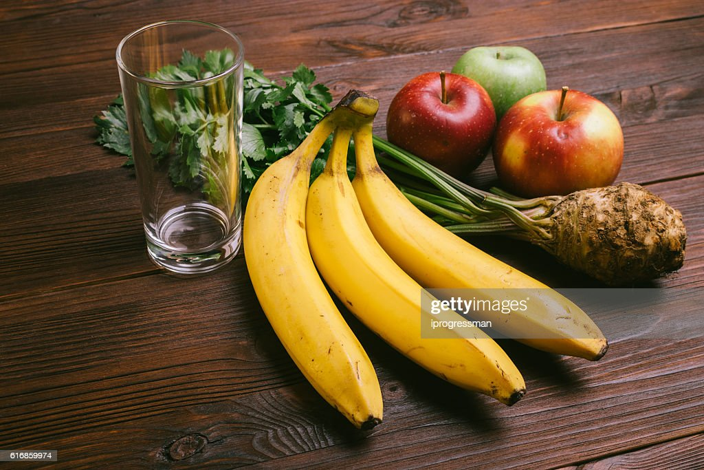 Empty glass, apples, celery root and bananas : Stock Photo