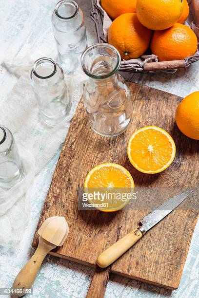 Empty glass bottles and sliced orange on wooden board