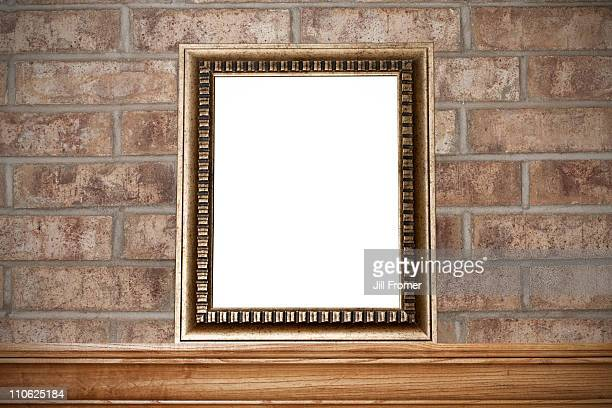 Empty gold photo frame on mantelshelf & brick wall
