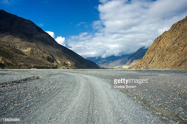 Empty gravel road with mountains